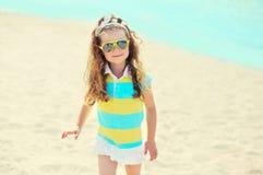 暑假,旅行概念-海滩佩带的太阳镜的小女孩孩子 库存照片