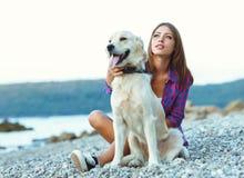 暑假,有一条狗的妇女在海滩的步行 免版税库存图片