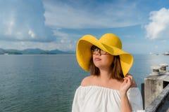 暑假,戴黄色帽子的愉快的妇女在沿海岸区码头 安达曼海Ranong,泰国 图库摄影