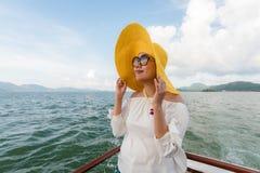 暑假,戴黄色帽子的愉快的妇女在游艇 安达曼海泰国 免版税库存照片