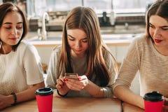 暗中侦察为他们的朋友的两名好奇妇女 免版税库存图片