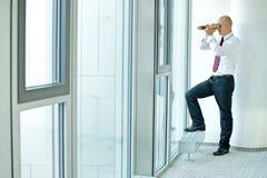 暗中侦察使用望远镜的白种人商人通过办公室窗口 库存图片