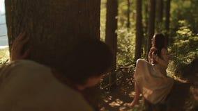 暗中侦察在美丽的森林若虫的年轻喀尔巴阡山脉的乡民,当梳她的辫子时的她 不可思议的世界喀尔巴阡山脉 影视素材
