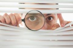 暗中侦察通过与寸镜的路辗窗帘的男性眼睛 免版税库存图片
