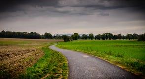 黑暗和有风道路在秋天 免版税图库摄影