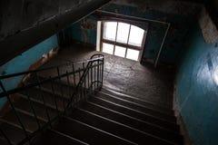 黑暗在老生存房子里放弃了楼梯内部 免版税库存图片