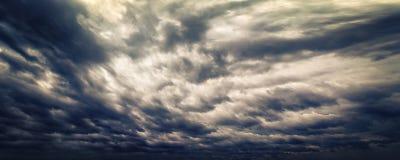 黑暗的与轻的瞥见的晚上风雨如磐的天空 免版税库存照片