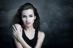 黑暗的云彩背景的孤独的妇女  库存照片