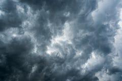 黑暗的云彩,阳光背景在雷暴前的通过非常黑暗的云彩背景,在旋风的白色孔dar 免版税库存图片