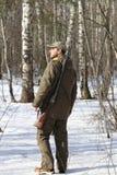 黑暗的卡其色的衣物的猎人人在森林里 库存照片