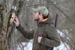 黑暗的卡其色的衣物的猎人人在森林里 免版税库存图片