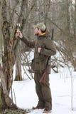 黑暗的卡其色的衣物的猎人人在森林里 免版税库存照片
