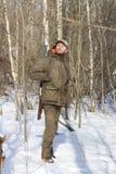 黑暗的卡其色的衣物的猎人人在森林里 免版税图库摄影
