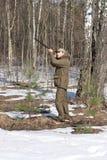 黑暗的卡其色的衣物的猎人人在森林里 图库摄影