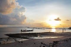 黑暗的在背景小船的海热带日落 免版税库存照片