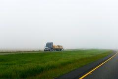 黑暗的大半船具卡车平床拖车木材货物有雾的路 免版税图库摄影