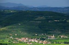 黑暗的山背景的晴朗的村庄 免版税库存图片