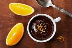 从黑暗的巧克力沫丝淋的可口点心与橙色切片装饰了柑橘果皮 免版税库存图片