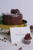 黑暗的巧克力蛋糕用曲奇饼和杯形蛋糕莓果在白色木背景 字法 明信片 库存照片