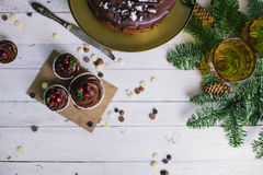 黑暗的巧克力蛋糕用曲奇饼和杯形蛋糕莓果在白色木背景 免版税库存照片