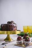 黑暗的巧克力蛋糕用曲奇饼和杯形蛋糕莓果在白色木背景 免版税图库摄影