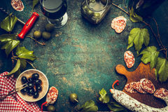 黑暗的意大利食物和开胃小菜背景用酒、蒜味咸腊肠、橄榄和厨房工具,顶视图,框架 库存照片