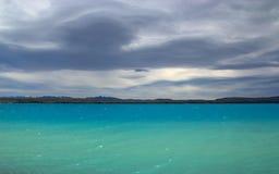 黑暗的普卡基湖云彩盘旋的鲜绿色表面  库存照片