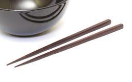 黑暗的木筷子和陶瓷碗 图库摄影