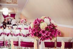 黑暗的桃红色花束在富有的饭桌上的白色花瓶站立 库存图片