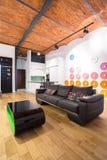 黑暗的沙发和颜色坐垫 免版税库存照片