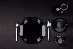 黑暗的现代minimalistic餐馆菜单嘲笑与黑光滑的板材,匙子,叉子,杯子,顶视图 免版税库存照片