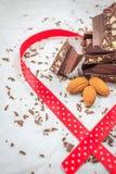 黑暗的用红色丝带装饰的巧克力和杏仁 免版税库存图片