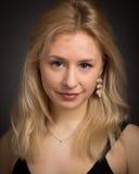 黑暗的白肤金发的年轻微笑的妇女 免版税库存图片