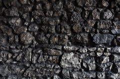 黑暗的石墙由不规则和粗砺的岩石做成 库存照片