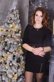 黑暗的礼服的年轻美丽的深色的妇女在圣诞节, w 免版税库存照片