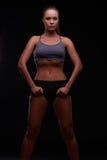 黑暗的背景的女孩参与健身 免版税库存图片
