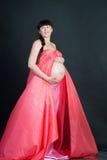 黑暗的背景的怀孕的深色的妇女 免版税库存图片