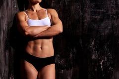 黑暗的背景的肌肉妇女 免版税库存图片