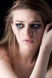 黑暗的背景的年轻哭泣的妇女 免版税库存图片
