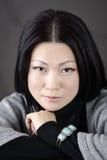 黑暗的背景的年轻美丽的亚裔女孩 免版税库存图片