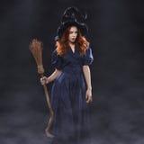 黑暗的雾的年轻美丽的红发巫婆 库存图片