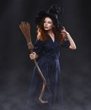 黑暗的雾的年轻美丽的红发巫婆 免版税库存照片