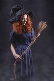 黑暗的雾的年轻美丽的红发巫婆 免版税库存图片