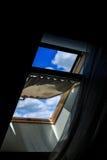 黑暗的顶楼的窗口,开放 清楚的蓝天的看法与云彩的 图库摄影