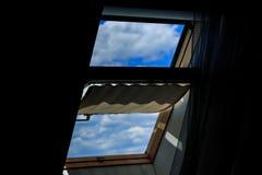 黑暗的顶楼的窗口,开放 清楚的蓝天的看法与云彩的 免版税库存照片