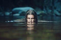 黑暗的水中女仙带着强烈的凝视 库存图片