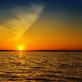 黑暗的水和橙色日落 免版税库存照片