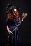 黑暗的年轻美丽的红发巫婆 免版税图库摄影