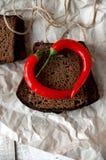 黑暗的黑麦面包片断用在一张被弄皱的纸的辣椒 图库摄影