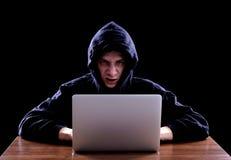 黑暗的hoody开会的黑客在笔记本前面 免版税库存图片